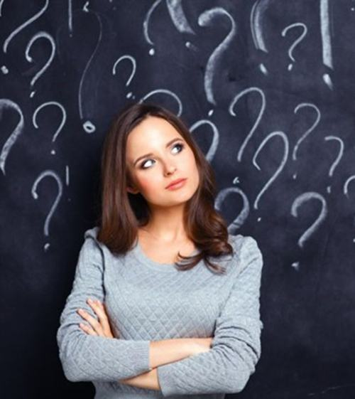 woman crossing her arms in front of chalkboard covered in questions marks