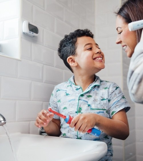 Mother and son brushing teeth to prevent dental emergencies