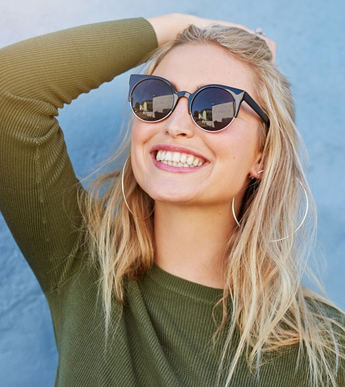young woman wearing sunglasses and smiling with veneers in North Grafton